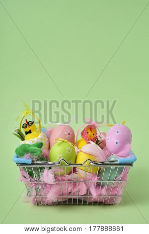 a pile of different decorated easter eggs, a couple of teddy chicks and some pink feathers in a basket against a green background, with a blank space above them