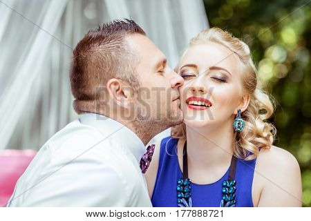 Close up view man and woman sitting on the bed and man kissing a woman in cheek in the lawn in Lviv, Ukraine.