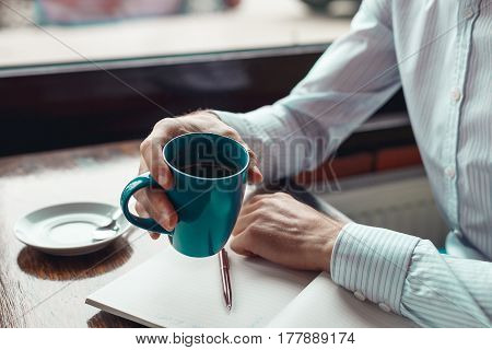 Close up coffee break businessman hands holding mug of coffee. A man in formal clothes works outside the office.