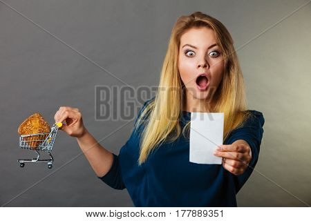 Shocked woman holding shopping basket with bread looking at bill receipt being scared of huge prices