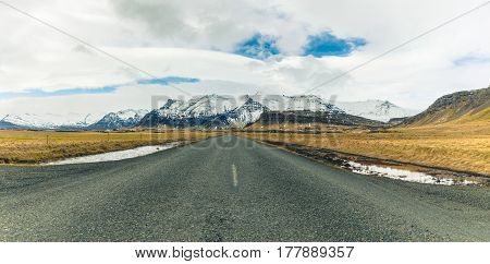 Empty Countryside Road In Iceland With Mountains On Background