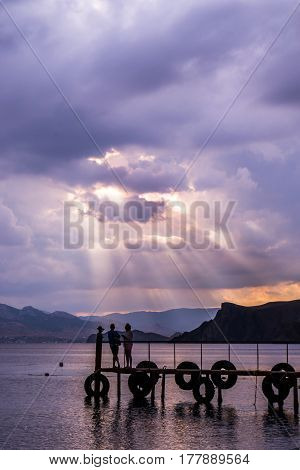 Silhouettes of men and women standing on the pier in the background of mountains and sea stress-rays of the setting sun. Romantic atmosphere and natural beauty of a meditation relaxation meditation expression of feelings.