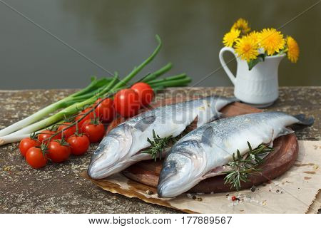Fresh seabass, vegetables and spices on the table