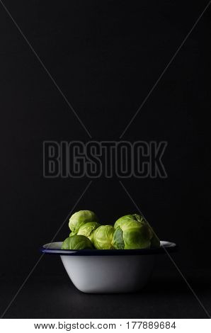 Brussel Sprouts Piled High In Enamel Baking Tin On Black Background