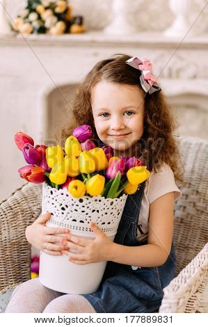 Girl with curly hair smiling and posing with a large bouquet of flowers in white vase. Mother day concept