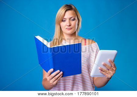 Modern education devices for reading books learning choice concept. Blonde woman choosing between book and tablet. Studio shot on blue background.