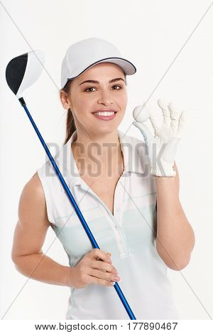 Pretty woman golfer posing with golf club and ball on white background in studio