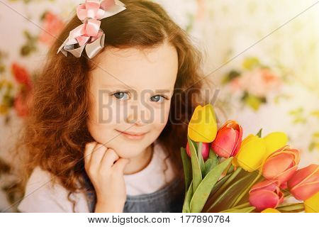 Little girl smiling and posing with a large bouquet of flowers. Mother day concept