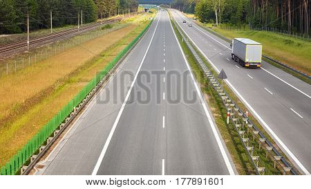 Panoramic picture of a lorry on almost empty highway.
