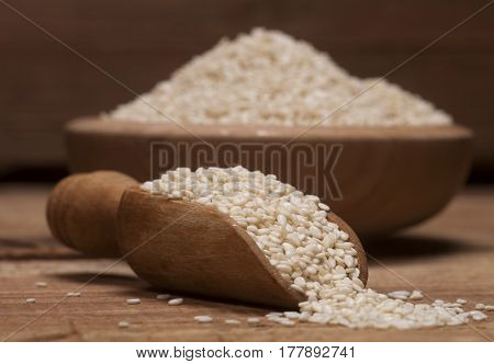 Fresh Sesame Seeds In A Wooden Bowl And Spoon