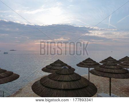 Parasols on the beach after sunset, Porec, Istria, Croatia