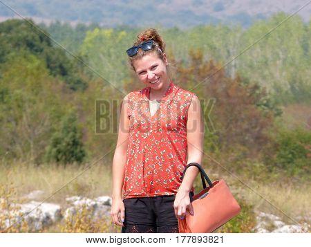 Merry girl in red background of European nature in Varna, Bulgaria