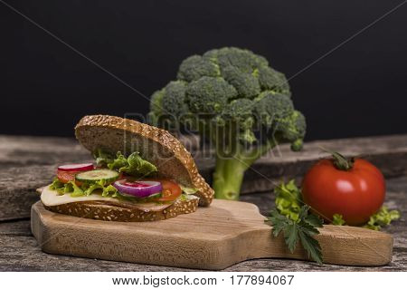 Healthy sandwich made with whole grain bread lettuce tomato radish cheese and roasted chicken slices.