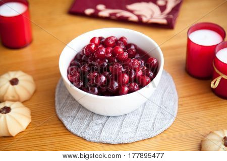 Red berries Cranberries with biscuits and red candles on a wooden table
