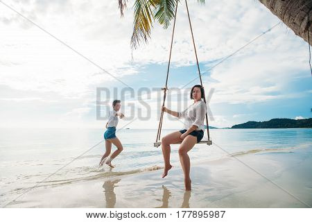 Happy woman on a swing while daughter is running next to her tropical island phu quoc