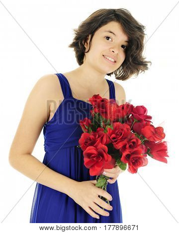 Young teen girl in a formal blue dress. She's holding a bouquet of red flowers.