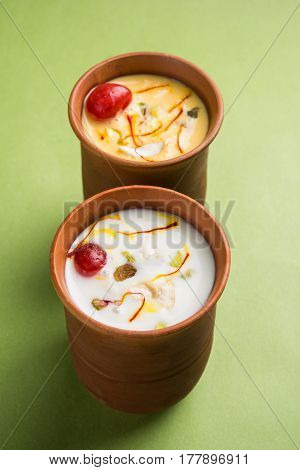 Authentic Indian cold drink made up of curd, milk & malai called Lassi in saffron / kesar flavour, also called kesariya or keshariya or kesar lassi, served in traditional indian terracotta glasses poster