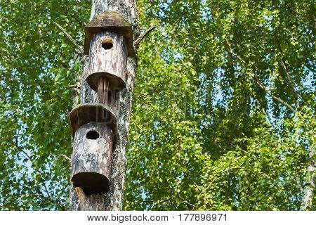 Two simple old birdhouse in a rustic style. Concept of the season, guest house, own housing, Dormitory, multi-storey building, townhouses, natural materials. For background, backdrop, substrate, composition use