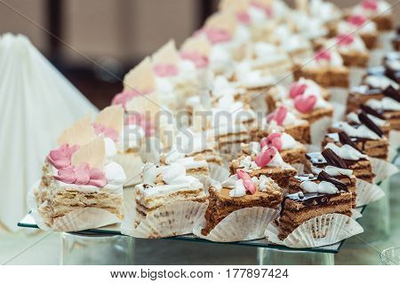 Cute candy bar with various candies and cakes. Wedding candybar on glass stand