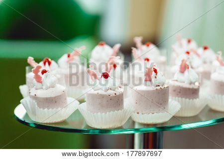 Pink craemy cakes on a glass stand. Close Up
