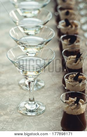 Beautiful row line of martini on a party and a row of desserts