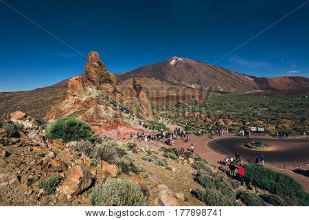 Volcanic landscape with tourists visiting volcano of Teide in Teide National park on Tenerife island, Spain