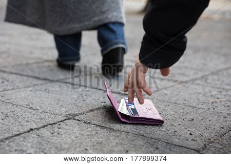 Close Of A Man Picking Up A Lost Purse On Street