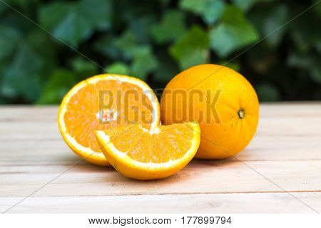 Fresh Ripe Oranges On Wooden Background. Exotic Juicy Mellow Fruit. In The Background Is Green Ivy P