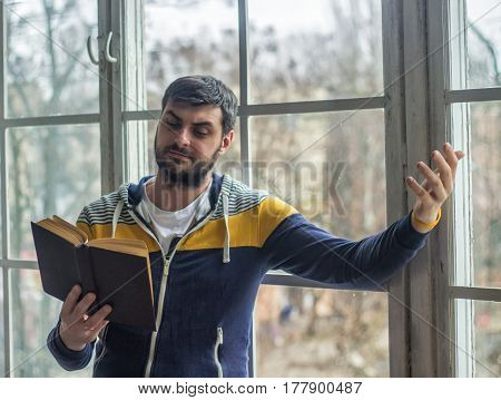 Bearded poet man reads a book with an expression gesture. Big window on background.