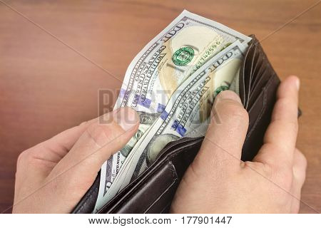 Close-up of male hand taking hundred dollar banknotes from wallet wooden background money and finance concept