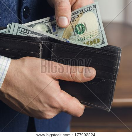 Close-up of male hands taking hundred dollar banknotes from wallet business and finance concept