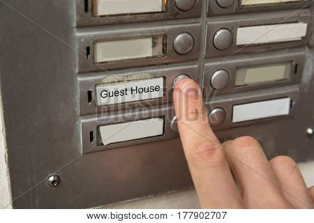 Close-up Of A Person Clicking On Door Bell Button Showing Guesthouse