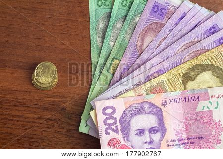 pack of ukrainian hryvnia banknotes and euro cent coins on wooden table devaluation concept