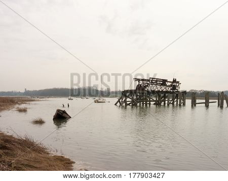 The river colne with a submerged boat and old structure.