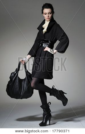 High fashion model in winter fur coat clothes with bag posing in the studio