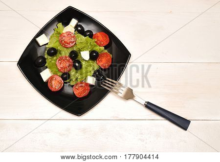 A greek salad on a wooden background
