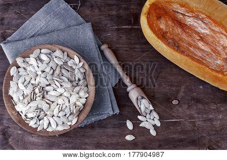 Pumpkin seeds in a wooden bowl next to a piece of fresh pumpkin