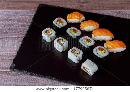 Large set of japanese rolls on a black stone plate Sushi rolls Japanese cuisine