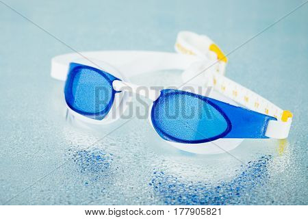 professional swimming glasses for training or competition, blue background