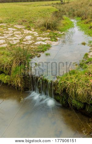 Small Stream Running On A Green Meadow With Stones And Smooth Water