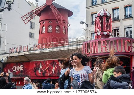 PARIS FRANCE - JUNE 8 2014: Tourists posing in front of Moulin Rouge one of the most famous Pigalle cabarets