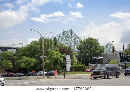 Montreal Quebec Canada - 18 July 2016 - Generic crossing and large streets in Montreal in summertime with Jacques-Cartier Bridge in the background. Modern style as editorial