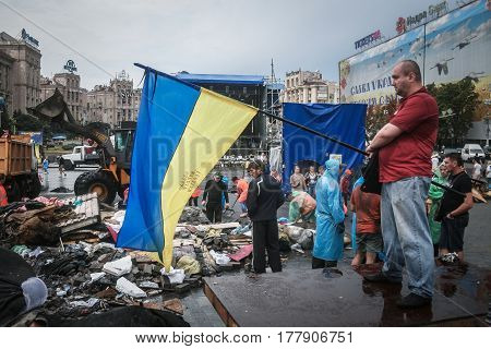KIEV UKRAINE - AUGUST 9 2014: Man waiving a Ukrainian flag on Maidan Square barricades during their removal
