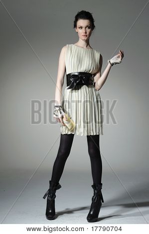 fashion model model holding little purse on gray background