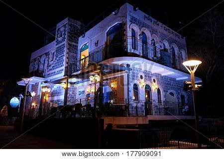 TIBERIAS ISRAEL - FEBRUARY 26 2017: Boutique Hotel Shirat Hayam (Song of the Sea) on the promenade in Tiberias in the night. Inscription: Boutique Hotel Song of the Sea