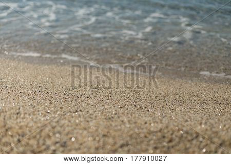 Beautiful sand at Kleopatra beach in Alanya turkey with sand in center of image in sharp focus and blurred wave and sand on foreground and background.