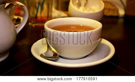 Pouried black tea in cup teapot and teaspoon. Tea time lunch snack breakfast dinner and supper relax concept.
