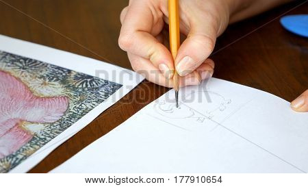 Female artist draws a pencil sketch drawing on paper in art studio. Student girl learning to draw and paint.