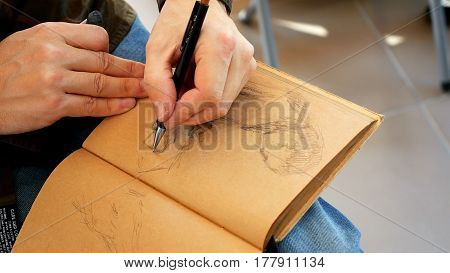 Graphic artist draws sketch picture artwork in scratch pad notebook manually with pencil.