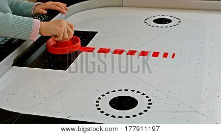 Little girl playing air hockey game with red mallet and puck